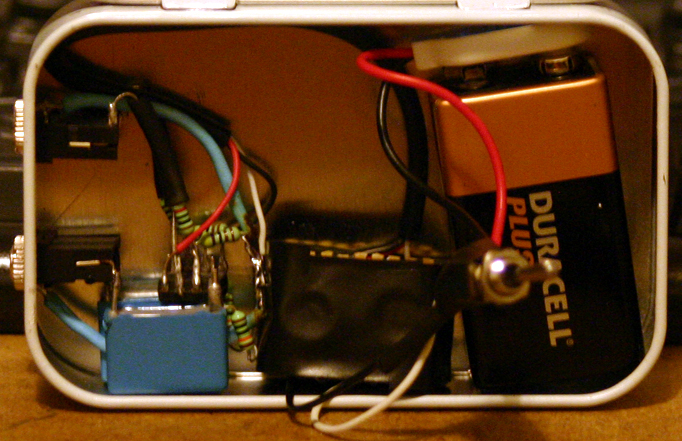 Wide view of the headphone amplifier in its tin